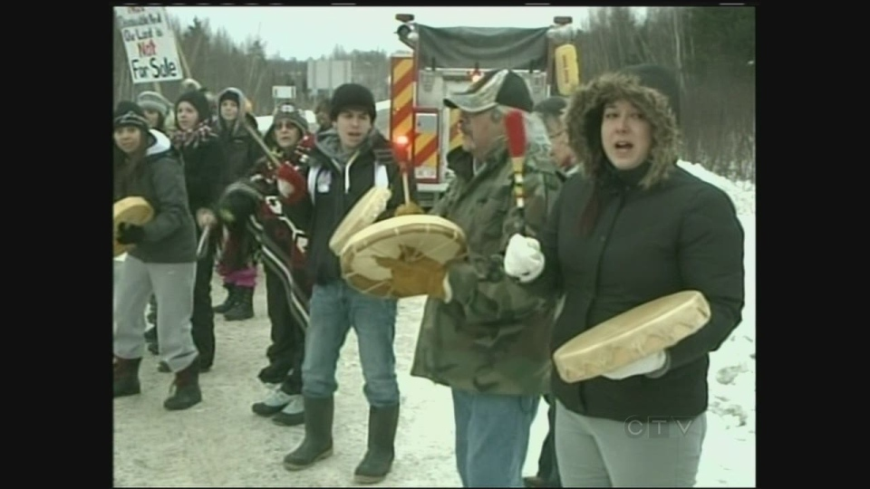 About three dozen people stood along Highway 102 at Kingsclear holding signs in opposition to the federal government's recently passed omnibus budget legislation, which they say eliminates treaty and aboriginal rights set out in the Constitution.