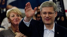 Prime Minister Stephen Harper waves as Newfoundland and Labrador Premier Kathy Dunderdale looks on during a campaign rally in St John's, Thursday March 31, 2011. (THE CANADIAN PRESS/Adrian Wyld)