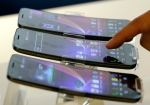 a visitor touches LG Electronics' smartphone G Flex displayed during a media event at its head office in Seoul, South Korea In this Tuesday, Nov. 5, 2013, file photo. (AP / Lee Jin-man)