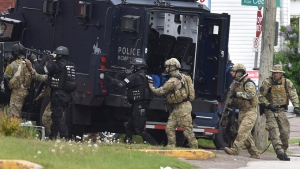 Heavily armed RCMP offers enter a residence during the manhunt for the shooting suspect in Moncton, Thursday, June 5, 2014. (Andrew Vaughan / THE CANADIAN PRESS)