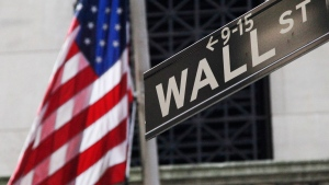 The American flag and a sign for Wall Street are shown outside the New York Stock Exchange, in New York, Monday, July 15, 2013. (AP / Mark Lennihan, File)