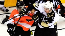 Pittsburgh Penguins' Sidney Crosby, right, shoves his glove and stick into the face of Philadelphia Flyers Brayden Schenn during a multi-fight brawl in front of the benches during the third period of Game 3 in a first-round NHL Stanley Cup playoffs hockey series, Sunday, April 15, 2012, in Philadelphia. (AP / Tom Mihalek)