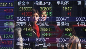 People are reflected on the electronic board of a securities firm in Tokyo, Tuesday, Dec. 30, 2014. (AP / Koji Sasahara)