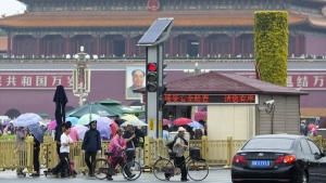 Visitors cross the road near a security check point into Tiananmen Square on a rainy day in Beijing, Thursday, June 4, 2015. (AP / Ng Han Guan)