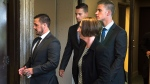 Simon Radford, Joshua Finbow and Craig Stoner, left to right, British sailors charged with sexual assault causing bodily harm while visiting for a hockey tournament earlier in the year, head from Nova Scotia Supreme Court with an unidentified woman on Tuesday, Aug. 11, 2015. (Andrew Vaughan / CANADIAN PRESS)