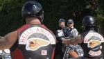 Police watch as Quebec members of the Hell's Angels motorcycle gang arrive at the White Rock, B.C., chapter's property in Langley, B.C., on July 25, 2008. (Darryl Dyck / The Canadian Press)
