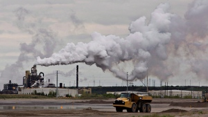 A dump truck works near the Syncrude oil sands extraction facility near the city of Fort McMurray, Alberta on Sunday June 1, 2014. (THE CANADIAN PRESS/Jason Franson)