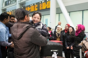 Six-year-old Ahmad Mazan Khabbaz, fourth from left, a refugee from Syria, smiles as he is greeted by family friend Rakan Almasri, himself a recent arrival to Canada from Syria, as the youngest member of his family arrives with his parents and sisters at Toronto's Pearson Airport, on Wednesday, Dec. 9, 2015. (Chris Young / THE CANADIAN PRESS)
