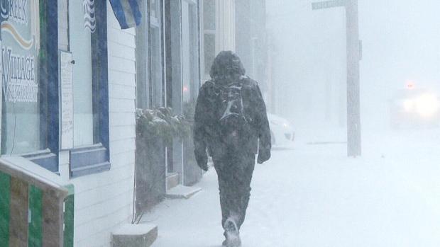 A pedestrian walks on a Halifax sidewalk during a blizzard on Monday, Feb. 8, 2016.