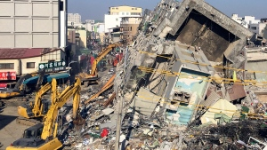 Rescue workers using excavators continue to search the rubble of a collapsed building complex in Tainan, Taiwan, Tuesday, Feb. 9, 2016. (AP / Annie Ho)