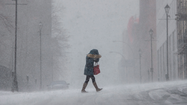 A woman shields her face from wind-swept snow during a winter storm in Halifax, NS on Monday, February 8, 2016. (THE CANADIAN PRESS/Darren Calabrese)