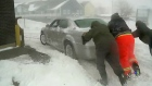 A group tries to get a car out of the snow in Cape Breton on Tuesday, Feb. 9, 2016.