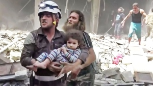 In this image made from video and posted online from Validated UGC, a Civil Defense worker carries a child after airstrikes hit Aleppo, Syria, Thursday, April 28, 2016 (Validated UGC via AP video)