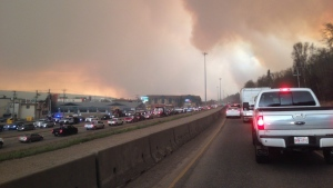 Smoke fills the air as cars line up on a road in Fort McMurray, Alberta on Tuesday May 3, 2016. (THE CANADIAN PRESS/Greg Halinda)