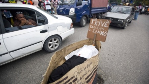 A man takes pictures from inside a taxi of a fake coffin that represents Provisional President Jocelerme Privert, with a sign that reads Creole 'Privert resign or die' during a protest in Port-au-Prince, Haiti on April 28, 2016. ( AP / Dieu Nalio Chery)