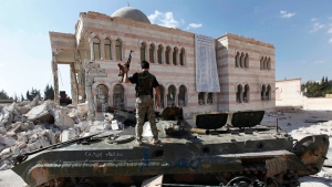 In this Sept. 23, 2012 file photo, a Free Syrian Army soldier stands on a damaged Syrian military vehicle in front of a damaged mosque in the Syrian town of Azaz, near Aleppo, Syria. (Hussein Malla / AP)