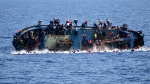 In this May 25, 2016 file photo made available by the Italian Navy, people try to jump in the water right before their boat overturns off the Libyan coast. Over 700 migrants are feared dead in three Mediterranean Sea shipwrecks south of Italy in the last few days as they tried desperately to reach Europe in unseaworthy smuggling boats, the U.N. refugee agency said Sunday, May 29, 2016. (Italian navy via AP Photo, file)
