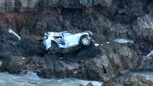 A vehicle sits at the bottom of a cliff off Maui's Hana Highway in Hana, Hawaii on May 29, 2016. (Tom Johnson via AP)