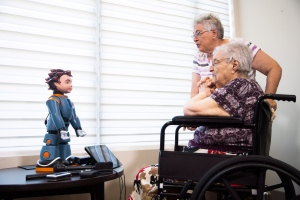 Elizabeth Graner, who has dementia, sits in her wheelchair as her daughter Penny Blake helps her interact with Ludwig, a two-foot-tall robot created by University of Toronto researchers to engage people with Alzheimer's disease and dementia, at a press conference on Tuesday, July 26, 2016. (THE CANADIAN PRESS/Michelle Siu)