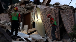 Rescuers search through debris following an earthquake in Pescara Del Tronto, Italy, Wednesday, Aug. 24, 2016. The magnitude 6 quake struck at 3:36 a.m. (0136 GMT) and was felt across a broad swath of central Italy, including Rome where residents of the capital felt a long swaying followed by aftershocks. (AP Photo/Andrew Medichini)