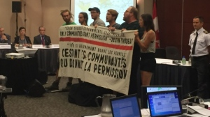 Protesters unfurl a banner denouncing the National Energy Board at public consultations into the Energy East pipeline on Aug. 29, 2016. (Photo: CTV News/Wayne Toplosky)