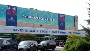 In this Sept. 21, 2016, photo, people stand outside the David S. Mack Sports and Exhibition Complex on the campus of Hofstra University in Hempstead, N.Y., at the site of the first presidential debate. (AP Photo/Frank Eltman).