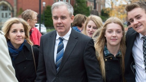 Dennis Oland and his wife Lisa, along with family members and friends, head from a bail hearing after being released from custody in Fredericton on Tuesday, Oct. 25, 2016. The New Brunswick Court of Appeal has ordered a new trial in the second-degree murder conviction of Oland in the 2011 bludgeoning death of his father, Richard Oland. (THE CANADIAN PRESS/Andrew Vaughan)