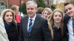 Dennis Oland and his wife Lisa, along with family members and friends, head from a bail hearing after being released from custody in Fredericton on Tuesday, Oct. 25, 2016. The New Brunswick Court of Appeal has ordered a new trial in the second-degree murder conviction of Oland in the 2011 bludgeoning death of his father, Richard Oland. THE CANADIAN PRESS/Andrew Vaughan