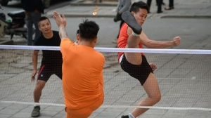 """Da cau"" or foot badminton players competing during a men's doubles game on the pavement of a street in downtown Hanoi