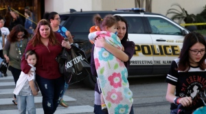 San Antonio police help shoppers exit the Rolling Oaks Mall, Sunday, Jan. 22, 2017, in San Antonio, after a deadly shooting. Authorities say several were injured after a robbery at the shopping mall. (AP Photo/Eric Gay)