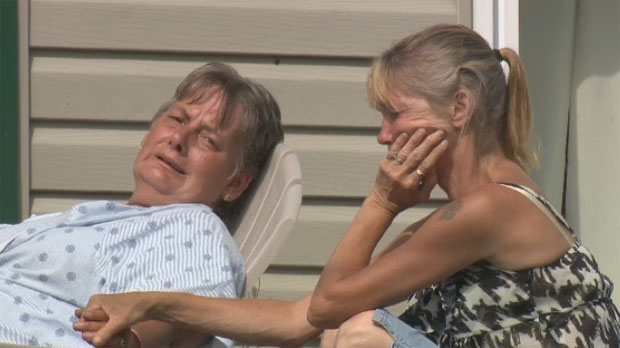 A neighbour comforts Carolyn Connors as she sits outside her apartment building.