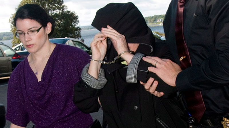 Melissa Ann Weeks, 77, of New Glasgow, N.S., also known as the 'Internet Black Widow,' leaves a Cape Breton Regional Police Services vehicle escorted by Const. Erin Donovan, left, and Const.Geoff MacLeod for a court appearance at the Sydney Justice Centre Tuesday, Oct. 2, 2012. (Vaughan Merchant / THE CANADIAN PRESS)
